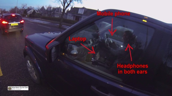 Araba kullanırken hem laptop hem akıllı telefon hem de kulaklık kullanan adam